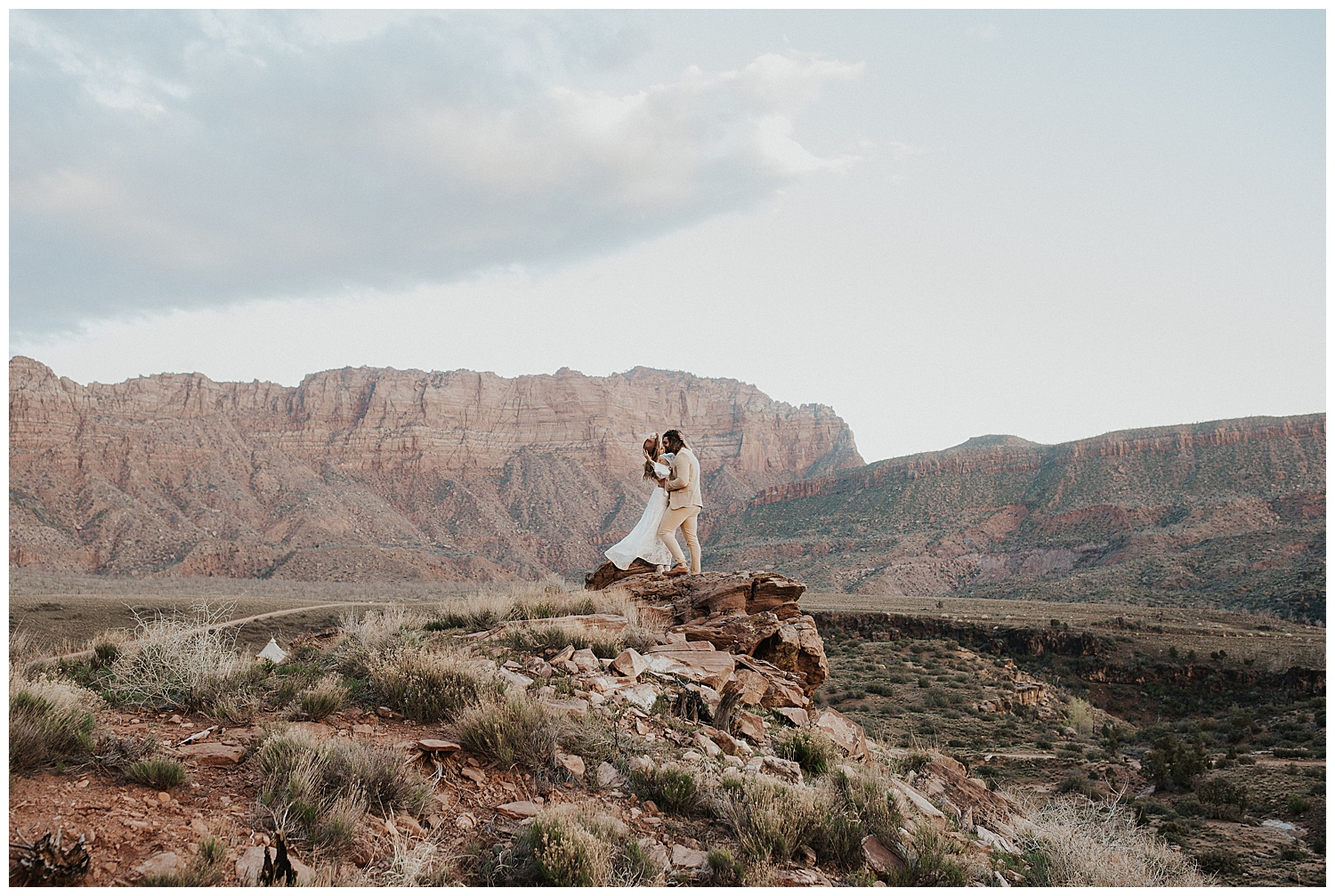 Couple kissing and embracing on a rock ledge with Utah's red cliffs in the background.